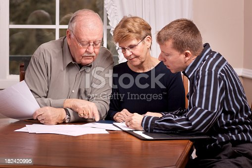 istock Financial advisor with senior couple going over paperwork 182420995