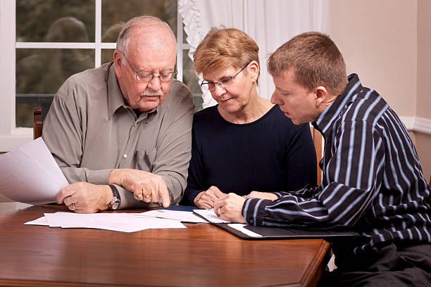 Financial advisor with senior couple going over paperwork stock photo