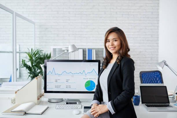 Financial analyst Portrait of young Asian business woman standing at computer with financial chart on it filipino ethnicity stock pictures, royalty-free photos & images