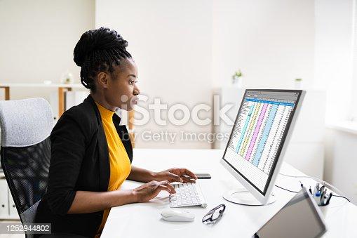 Financial Analyst Using Spreadsheet Software On Desktop Computer
