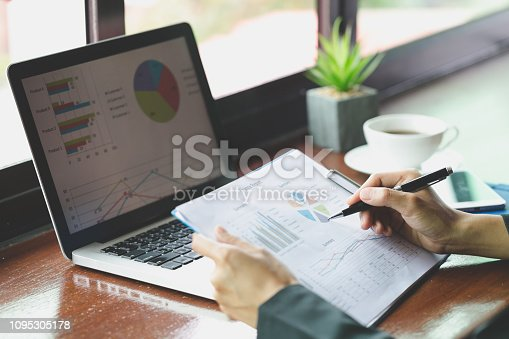 istock Financial analyst with document in his hands reading information on computer screen 1095305178