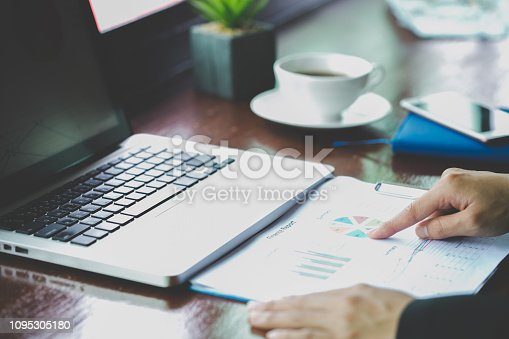613550610istockphoto Financial analyst with document in his hands reading information on computer screen 1095305180