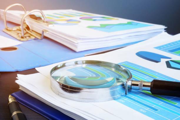 finanzielle auditbericht und lupe auf dem schreibtisch. - buchprüfung stock-fotos und bilder