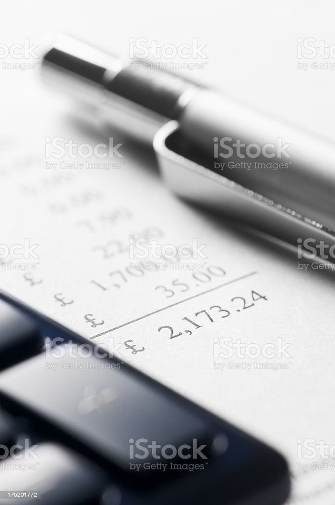 Financial calculations with a calculator and pen royalty-free stock photo