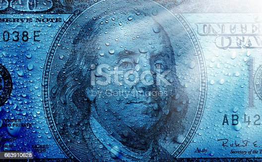 close up shot of one hundred dollar bill and water drops