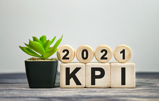 897644798 istock photo 2021 KPI - financial concept. Wooden cubes and flower in a pot. 1272552854