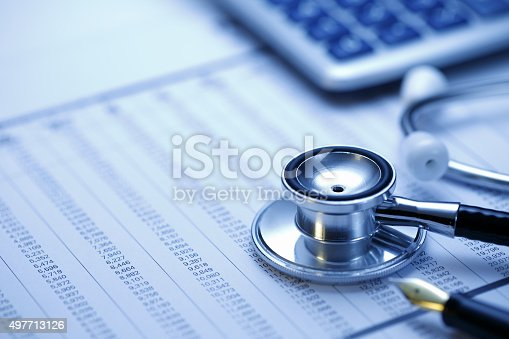 medical stethoscope and Calculator on financial data background ; shot with very shallow depth of field