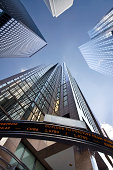Looking up at business buildings in a financial district with an electronic board displaying data and news.