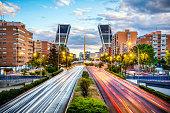car trails in paseo de la castellana avenue with kio towers at dusk in Madrid, Spain