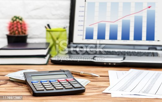 645670208istockphoto Financial documents, calculator, money and laptop on the office desk. Business report. 1176972887
