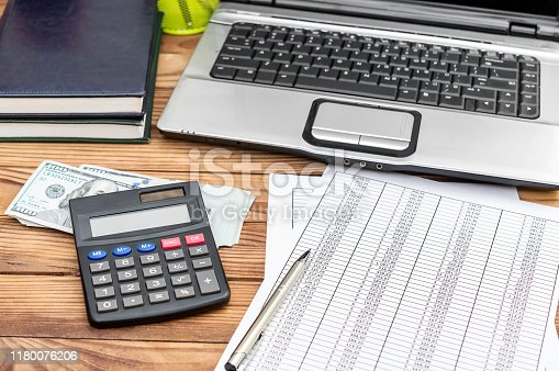 645670208istockphoto Financial documents, calculator, money and laptop on the office desk. Business report. 1180076206