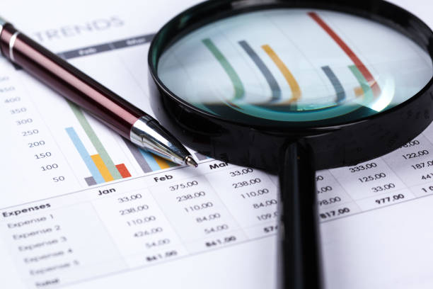 financial documents with magnifying glass over them - sale lenses stock photos and pictures