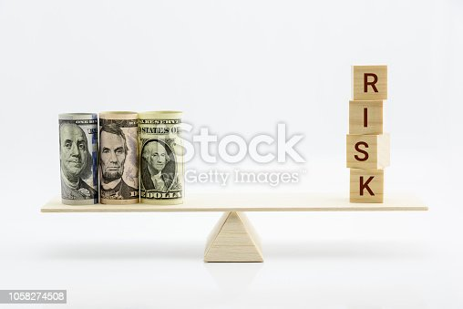 Financial, economic risk and risk perception, decision making concept : Dollar bills, risk wood blocks on a basic balance scale, depicts an uncertain event or condition that has an effect on objective