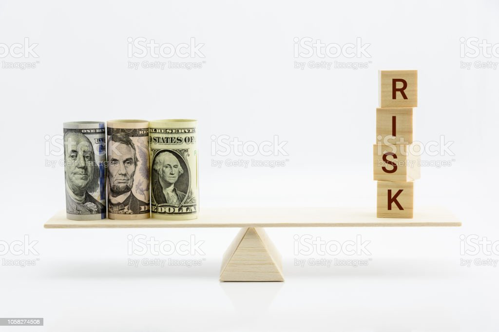 Financial, economic risk and risk perception, decision making concept : Dollar bills, risk wood blocks on a basic balance scale, depicts an uncertain event or condition that has an effect on objective stock photo