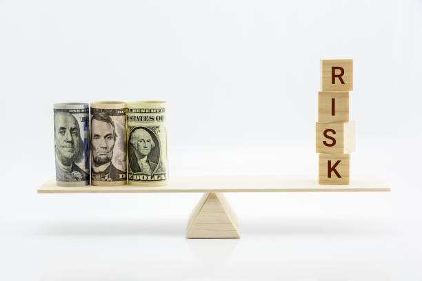 financial, economic risk and risk perception, decision making concept : dollar bills, risk wood blocks on a basic balance scale, depicts an uncertain event or condition that has an effect on objective - rischio foto e immagini stock