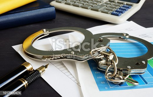 istock Financial fraud concept. Business documents and handcuffs. 1017300424
