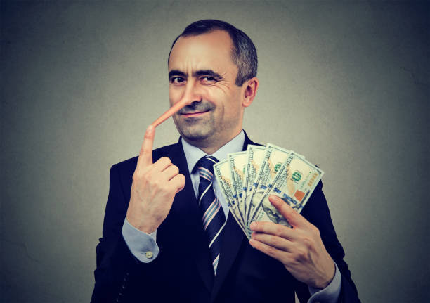 Financial fraud concept. Liar businessman with dollar cash Financial fraud concept. Liar businessman with dollar cash greed stock pictures, royalty-free photos & images