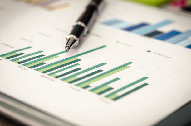 financial graphs  and pen - market research stock photos and pictures