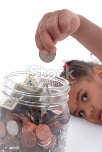 Girl saving her money in a glass jar.