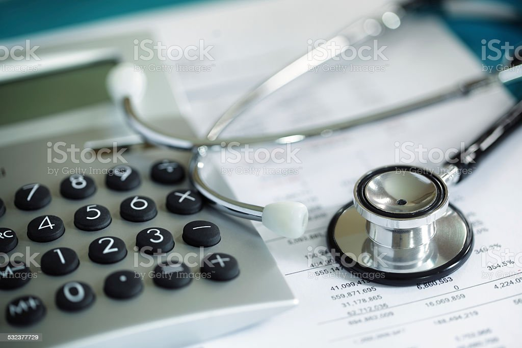 Calculator and stethoscope on financial statement concept for finance...