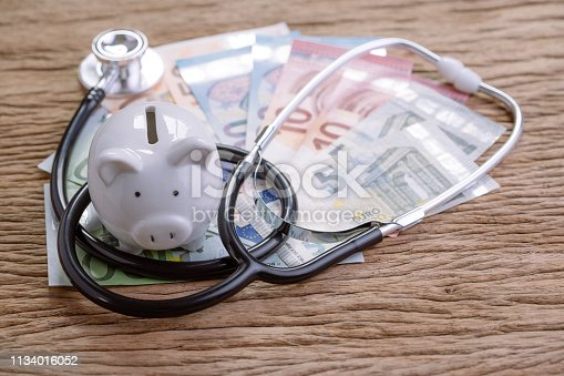 istock Financial health check or EU economic concept, saving white piggy bank with stethoscope on pile of Euro banknotes on wooden table, debt and finance crisis on Europe countrie 1134016052