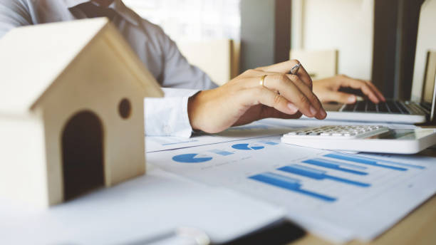 financial inspector making report,insurance agent analyzing about home investment loan at office room stock photo
