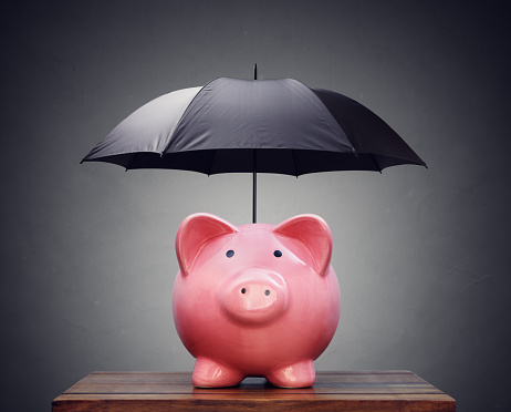 Piggy bank with umbrella concept for finance insurance, protection, safe investment or banking