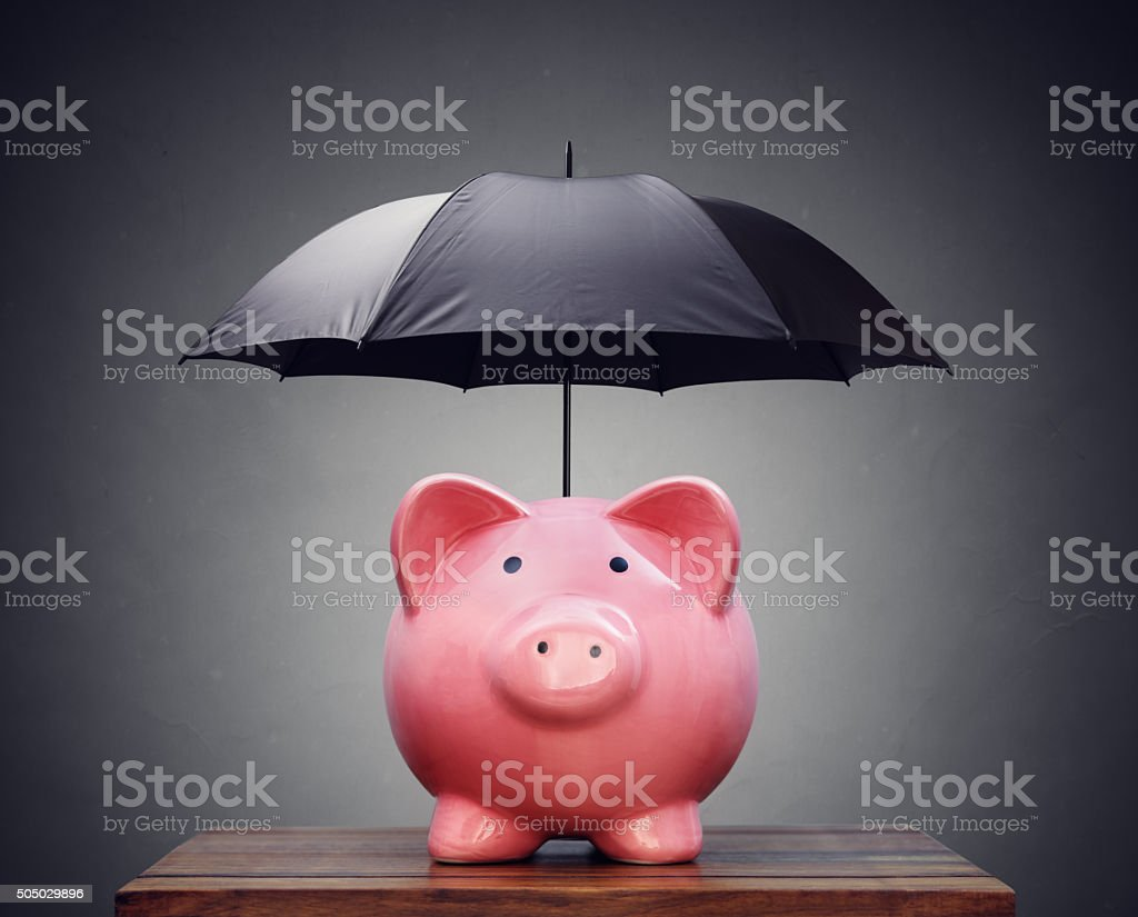 Financial insurance or protection piggy bank with umbrella stock photo