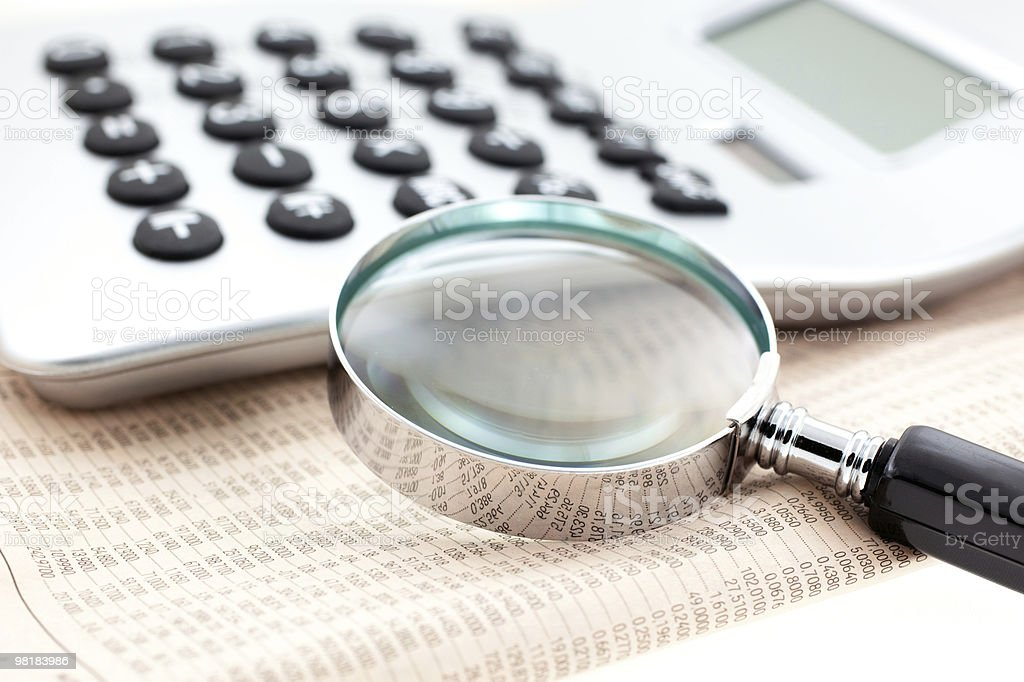 financial newspaper with calculator and magnifier royalty-free stock photo
