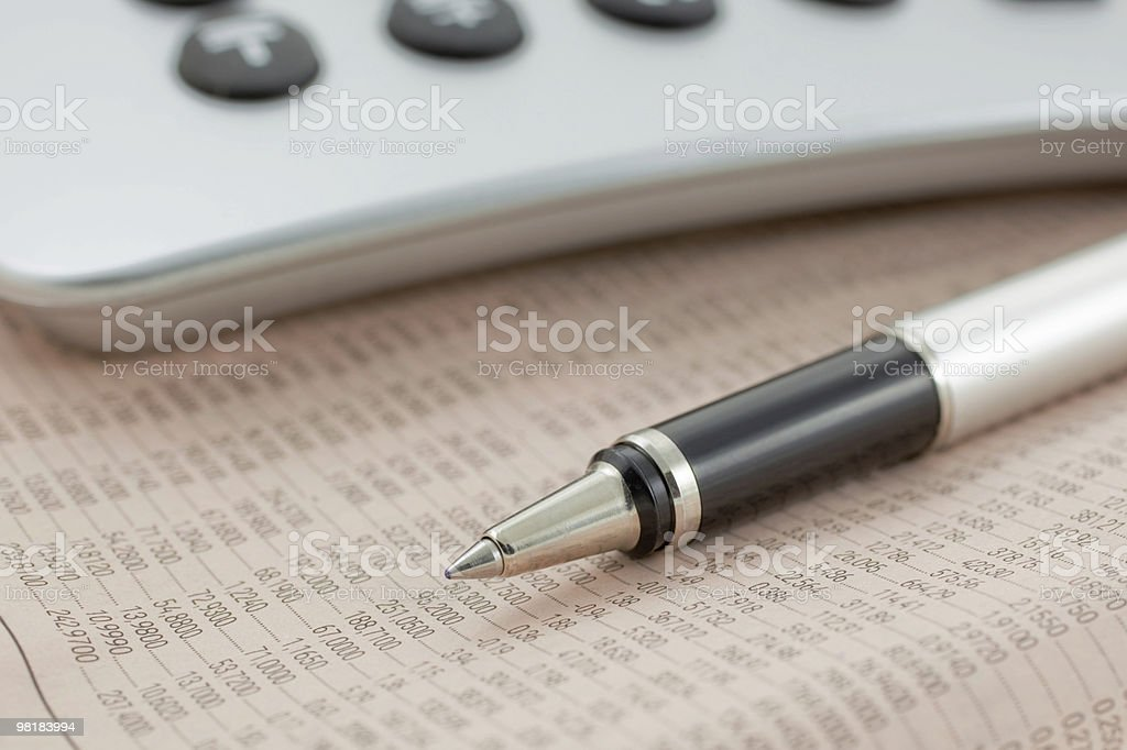 financial newspaper with calculator and pen royalty-free stock photo