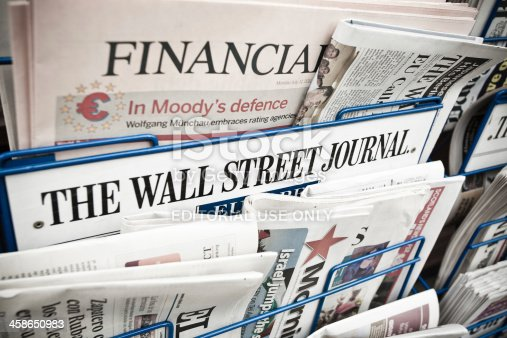 London, United Kingdom- July 11, 2011: Financial Newspapers on a Newsstand including the financial times, the Wall Street Journal and El Pais. The Financial Times (FT) is a morning daily newspaper published in London and printed in 24 cities around the world.