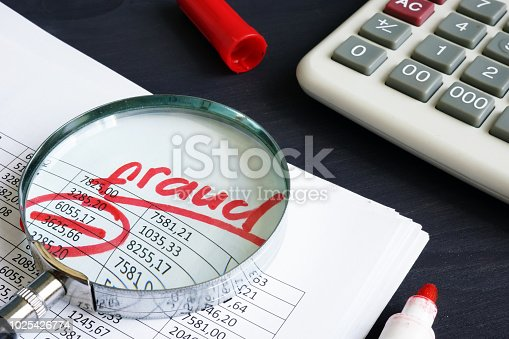 istock Financial or taxes fraud. Business report and magnifying glass. 1025426774