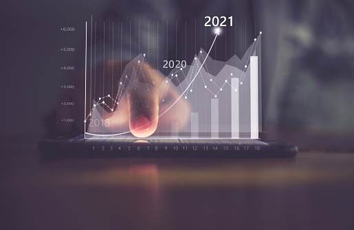 Augmented reality (AR) financial charts showing growing revenue In 2021 floating above digital screen smart phone, businesswoman having meeting about strategy for growth and success