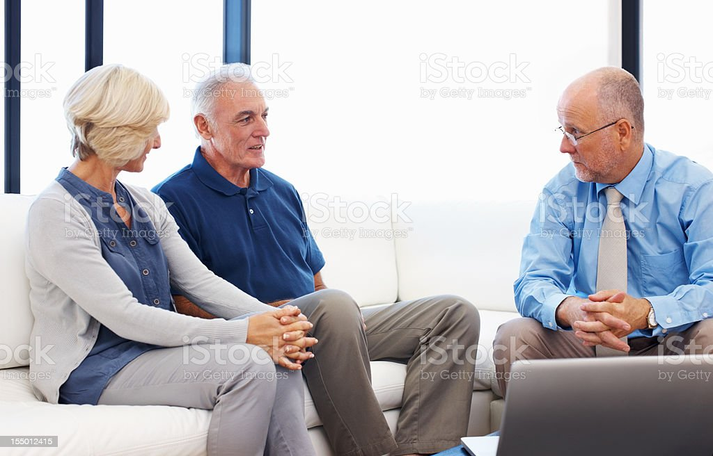 Financial planner consulting senior couple at home royalty-free stock photo