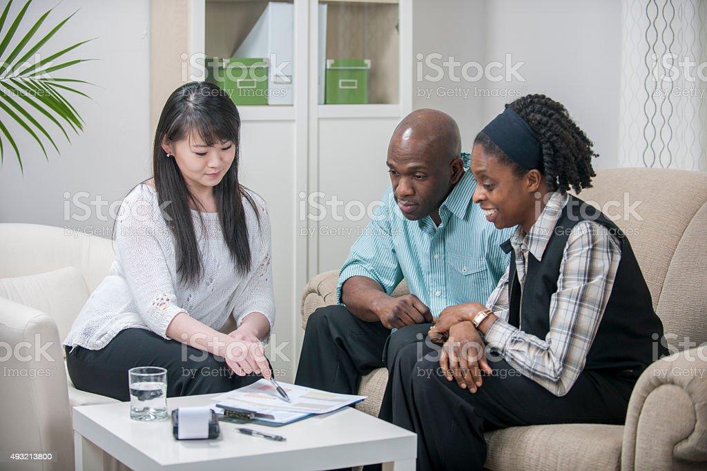 Planificador financiero ayudando a una pareja con su presupuesto - foto de stock