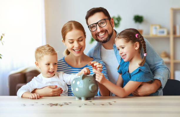 financial planning   family mother father and children with piggy bank at home - financial planning stock pictures, royalty-free photos & images