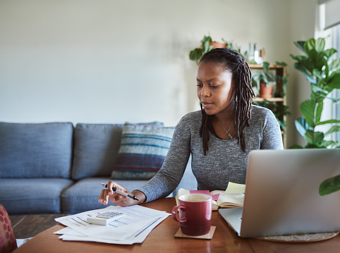 Shot of a young woman using a laptop and going through documents while working from home