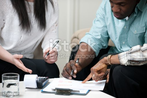 An African American couple meet with a financial planner in their home.  .