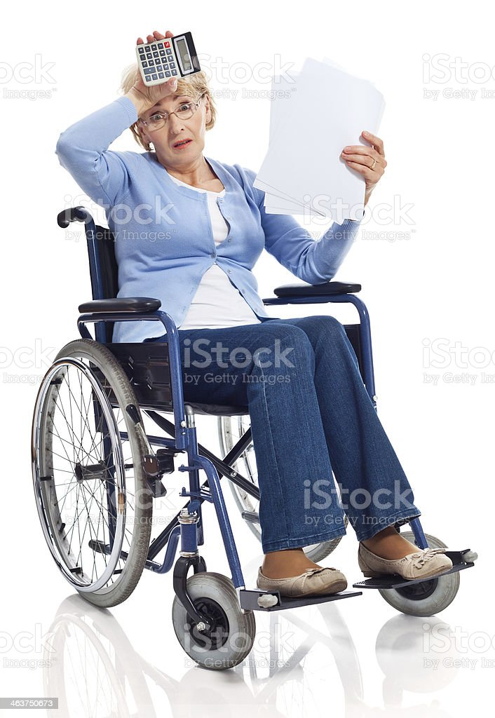 Financial problem Portrait of worried senior woman sitting in wheelchair and looking through bills. Studio shot on white background. 60-69 Years Stock Photo