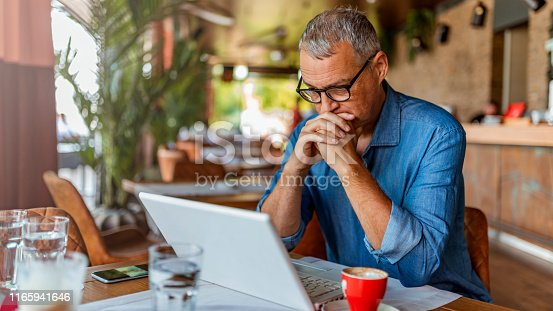 Contemplating businessman in the restaurant feeling sad. Full concentration on work. Confident mature man working on laptop while sitting at his working place in office. Mature Restaurant manager working on laptop, counting profit.
