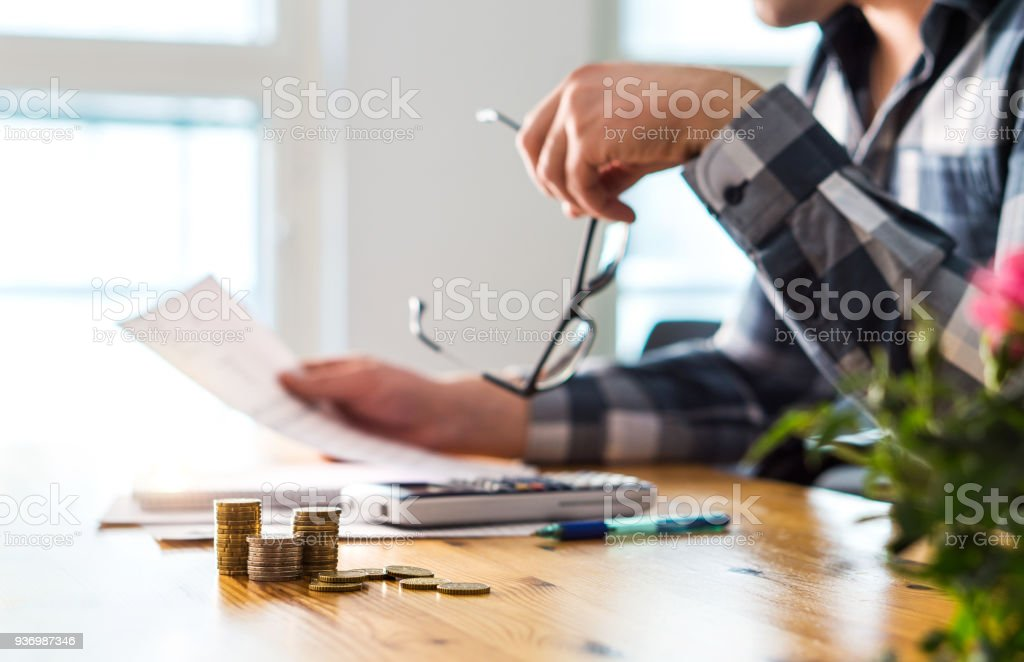 Financial problems, recession, bankruptcy or foreclosure concept. Unhappy sad man reading letter, bill, bank statement paper or tax document. stock photo