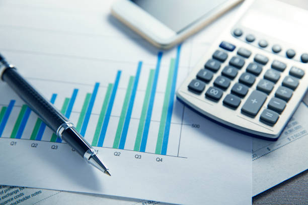 Financial Reports And Bar Graph A ballpoint pen and a calculator rest on top of a financial report that sits on a bar graph measuring a businesses quarterly performance. A mobile phone rests out of focus in the background. financial report stock pictures, royalty-free photos & images