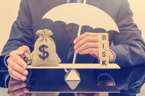 financial risk assessment / portfolio risk management and protection concept : businessman holds a white umbrella, protects a dollar bag on basic balance scale, defends money from being cheat or fraud - rischio foto e immagini stock