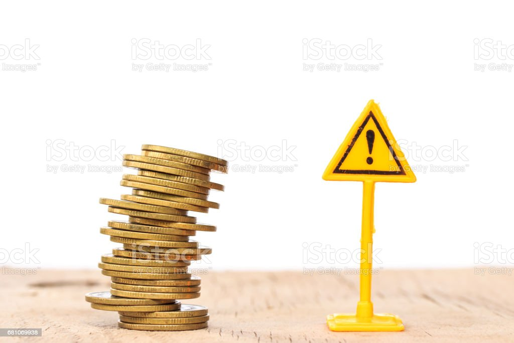 Financial risk. Coins falling and Warning label on whitebackground royalty-free stock photo