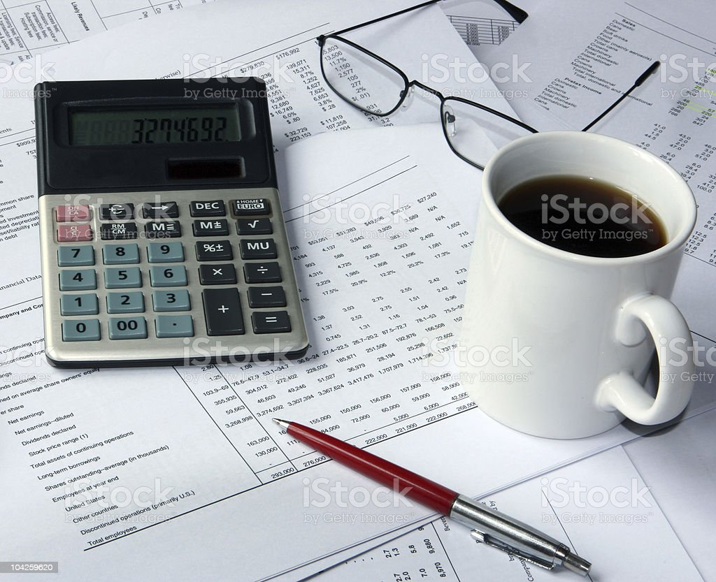Financial spreadsheets and calculator on accountant's desk royalty-free stock photo