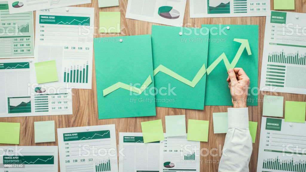 Financial success and green business Businessman composing a successful financial chart with arrow going up, he is using green paper cuts, eco business and financial success concept Adhesive Note Stock Photo
