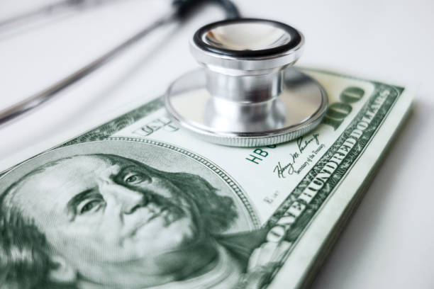 Financial survelliance Stethoscope on 100 dollar bills symbolizing financial surveillance expense stock pictures, royalty-free photos & images