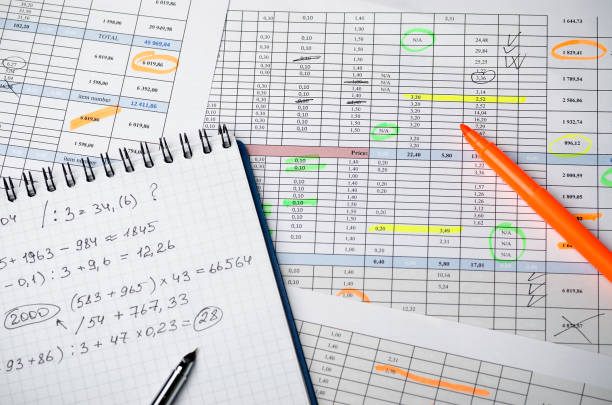 Financial tables on paper and a notebook with calculations