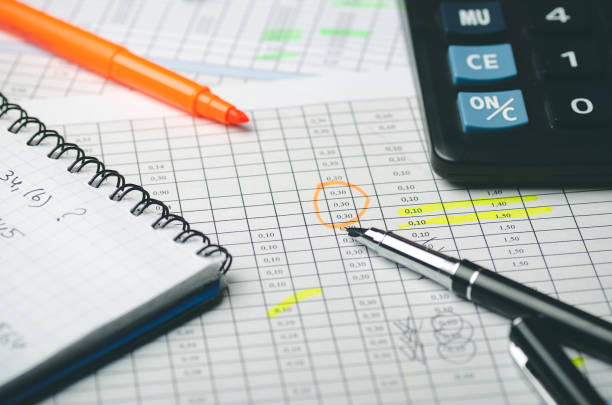 Financial tables on paper with notes, paper notebook, calculator and black pen