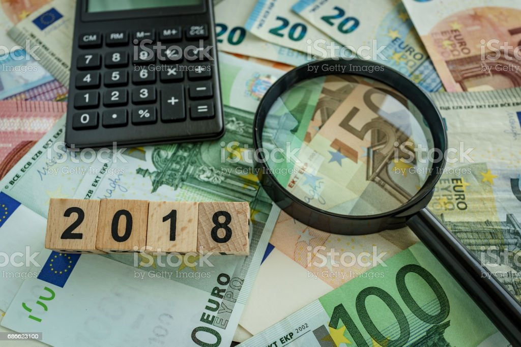 financial tax concept as magnifying glass on pile of euro banknotes, calculator and number 2018 on wooden block royalty-free stock photo